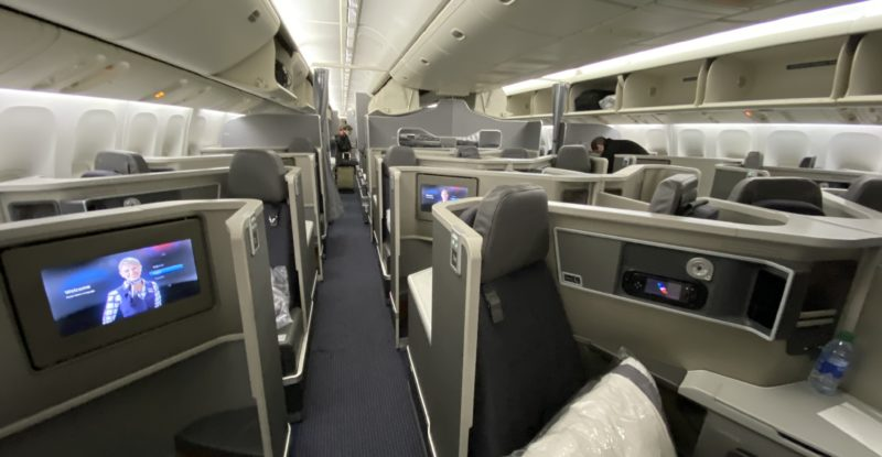 American Airlines business class show all greay interior with white pillows and some ife screens turned on