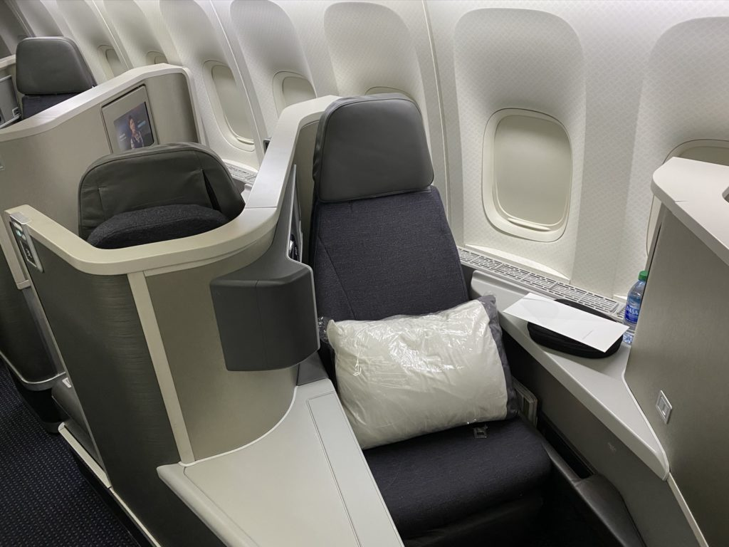 All grey business class seat with a white pillow wrapped in plastic and a menu card with a bottle of water.
