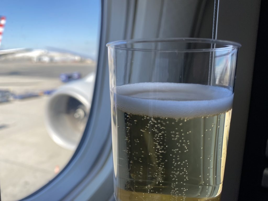 a glass of sparkling wine being held up in front of the aircraft windown which look out onto the engine