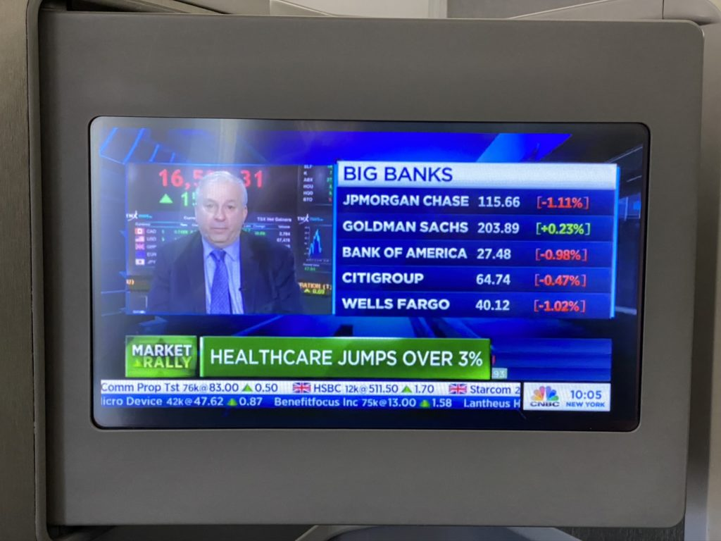 IFE Screen displaying and older man with big banks list and values and a headline that says health care jumps over 3%
