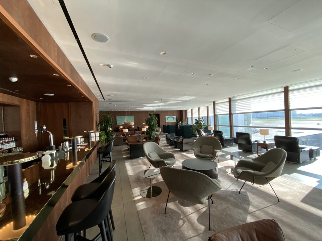 An empty lounge, including empty chairs and tables and an empty bar