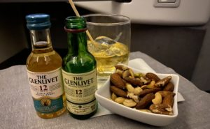 Two mini bottles of alcohol alongside a small white bowl full of nuts and a glass with ice on a tray table