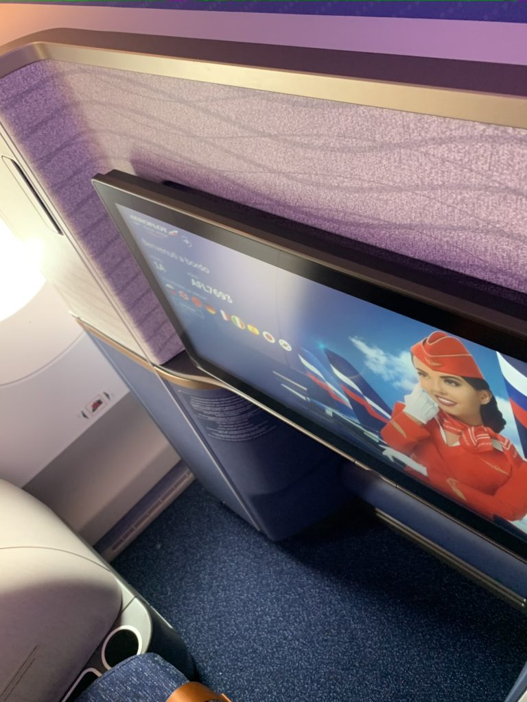 A photo of the Aeroflot Horizon suite with walls featuring a wave-like design and texture shrouding the large IFE screen