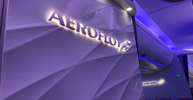 Bulkhead with white 3D brand element saying Aeroflot, with a purple LED-lit background with swirls