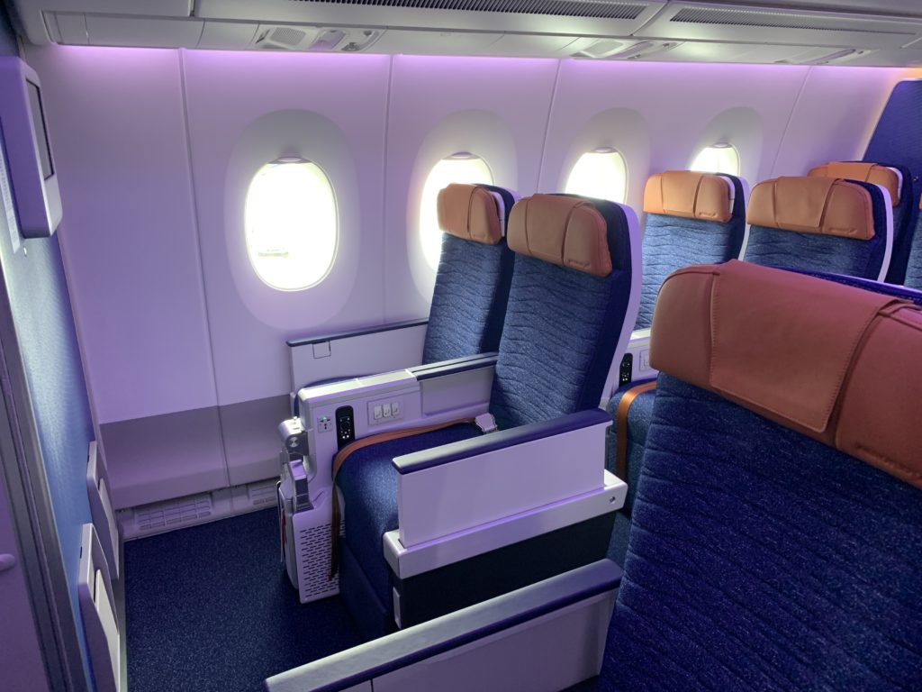 Aeroflot premium economy seats have both a luxurious and domestic fleet with blue seat covers and orange/bronze headrests. Seat rows are shown bathed in a pink/purple LED light