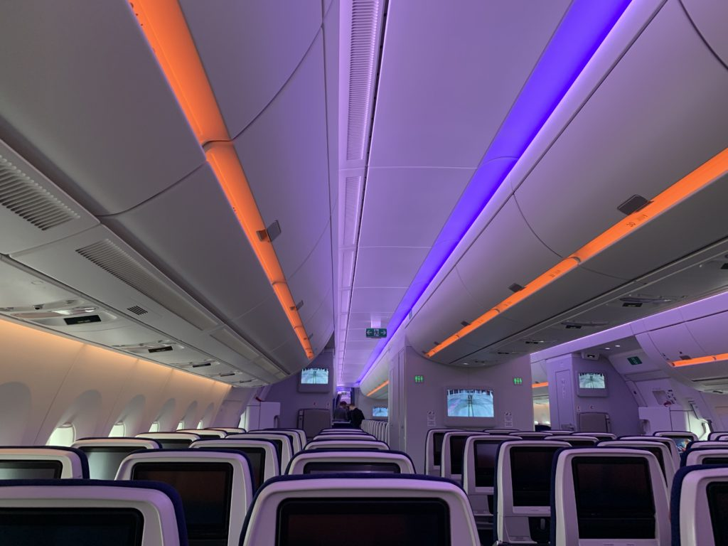 Purple and orange LED lights on the ceiling and overhead bins, seen above rows of economy class seats with seatback IFE