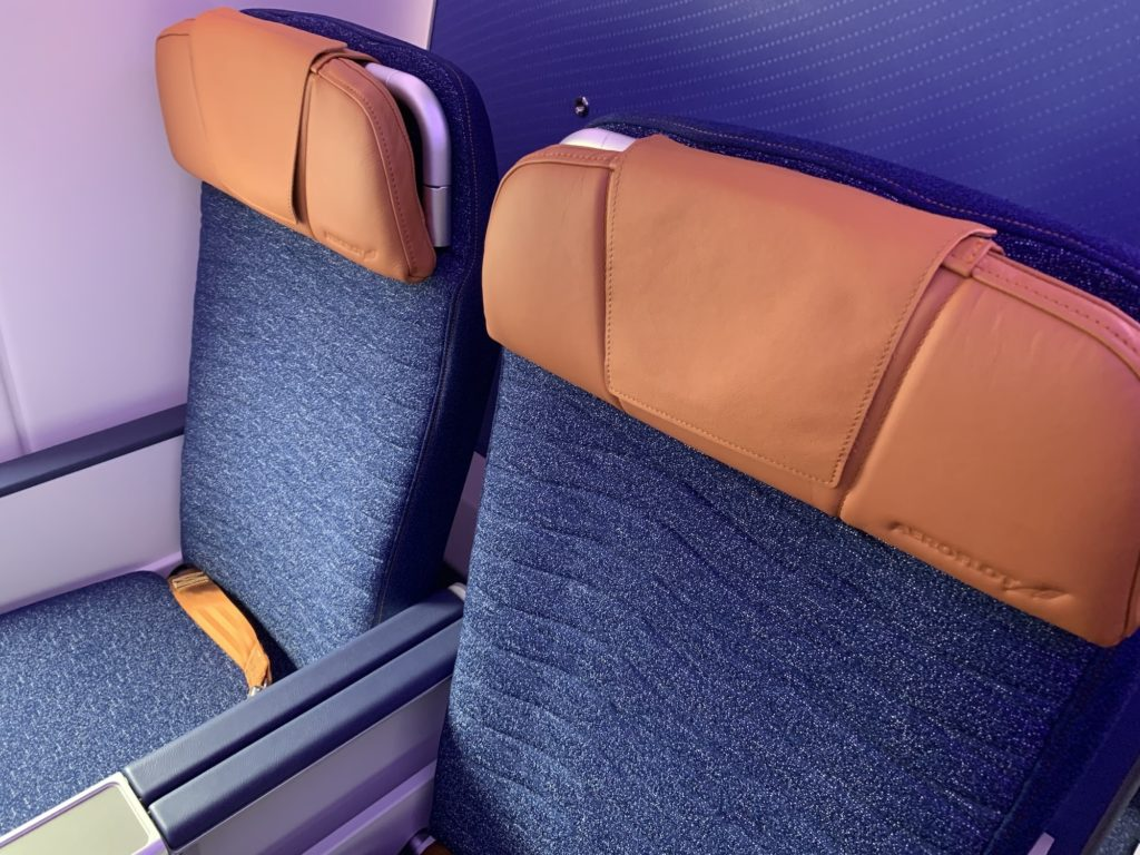 Two Aeroflot economy class seats with a wave-like design on the blue speckled seat covers with bronze headrests
