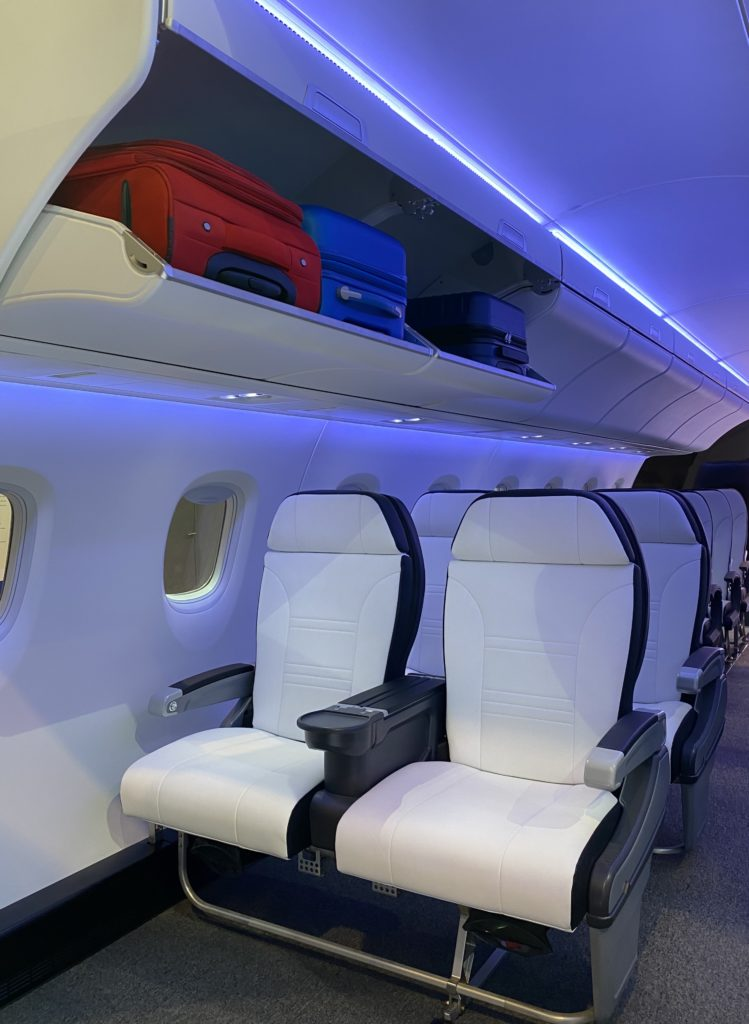 Rows of white leather premium seats with an open overhead bin showing red, blue and black carryon bags inside