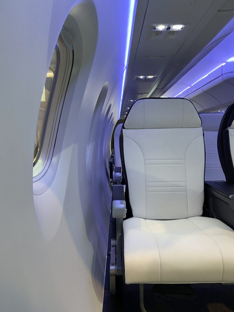 White leather type aircraft seat next to aircraft window with soft blue lighting around it