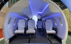 Mitsubishi M100 Cabin mock up on show floor showing 1-2 layout with soft blue lighting