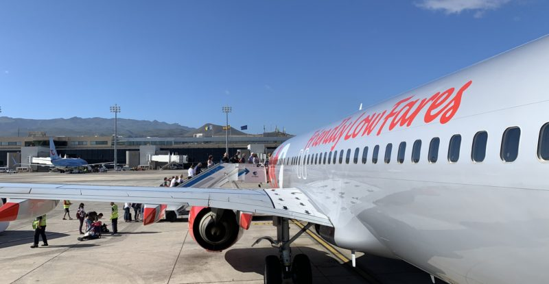 With the backdrop of a blue sky, a Jet2 aircraft sits parked with bright orange letters as part of its livery