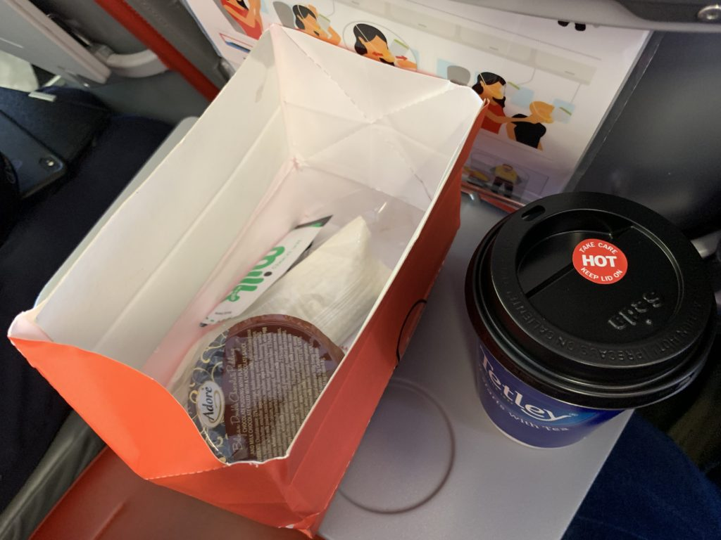 An inflight snack box containing cutlery, napkin and dessert, plus a cup of coffee on the tray table