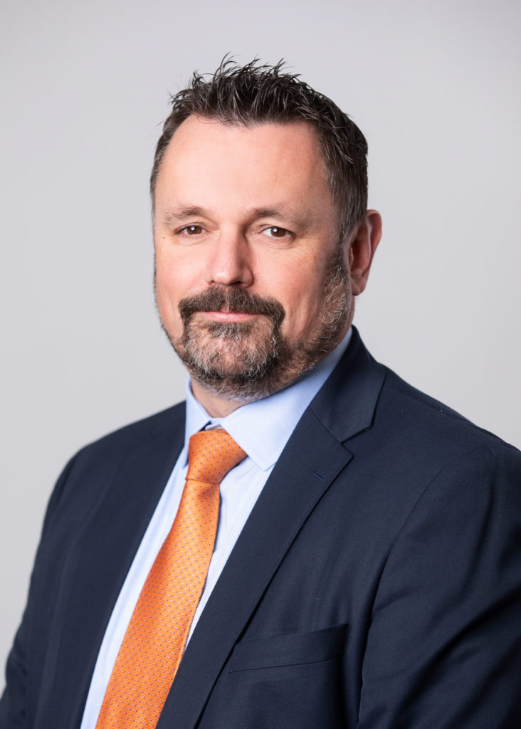 A photo of Neil Cairns with a blue jacket, orange tie, and a beard.