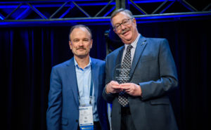 Bill Milroy, CTO of ThinKom Solutions, (left) accepts the Satellite Technology of the Year Award from Scott Chase, publisher emeritus of Via Satellite.
