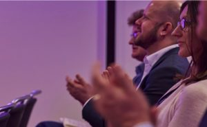 Men and women clapping at a conference