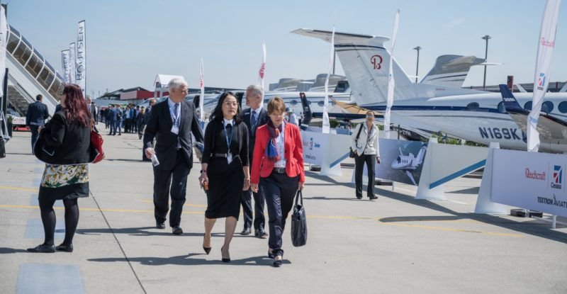 Static display of aircraft at the EBACE show. Men and women walking past the aircraft on display
