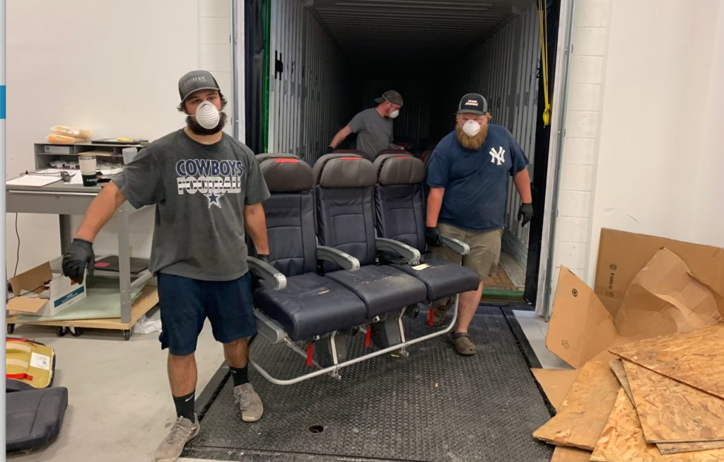 Two men wearing masks and carrying an aircraft seat triple out of a warehouse door