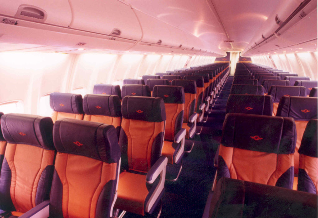 Rows of economy class seats on a Southwest Airlines 737 from years ago. The seats are orange-ish with blue headrests