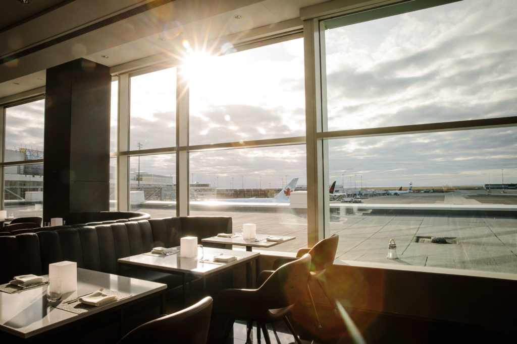 Sunlight shinning into the window over the lounge seating with the mountains and planes in the background