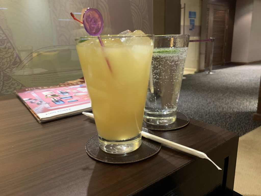 A yellow virgin piña colada in a glass with a purple plastic mixing straw