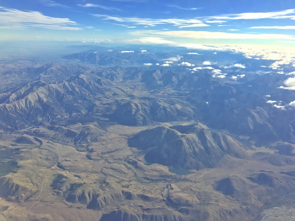 A photo of mountains and sky, seen through an aircraft window
