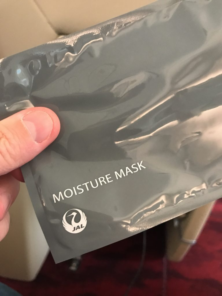 The Japan Airlines moisture mask packet - grey plastic with the JAL logo on it