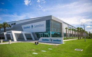 OneWeb Satellites JV facility in Florida with a blue sky in the background and green grass in the foreground