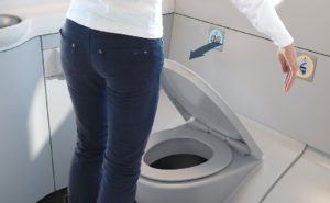A touchless lavatory as envisaged by Diehl. A woman places the back of her hand a few inches away from a sensor above the aircraft toilet, and the lid is seen closing
