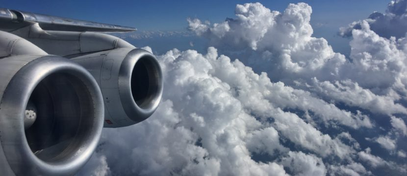 Looking out the window of a 747 to see the two giant engines, blue skies and fluffy white clouds