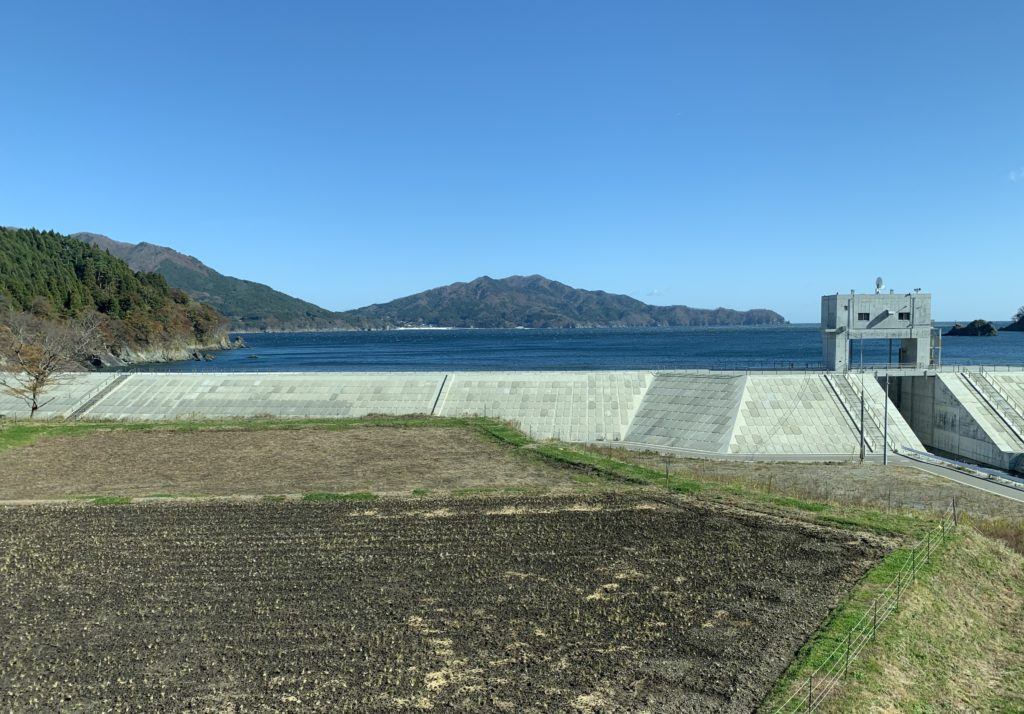 A bright blue sky serves as the back drop. A mountain and ocean is in view, as well as an ocean wall and closer in, a field with rows of small plants