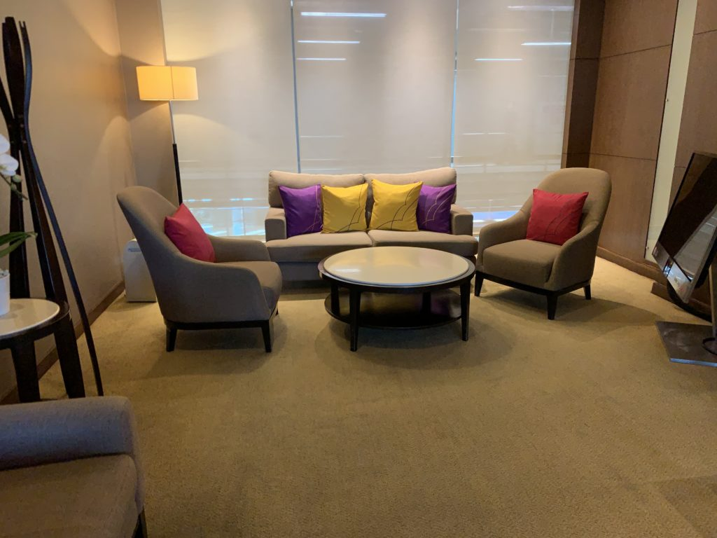 Two chairs and a love seat with multi-covered pillows in a semi-open space with a coffee table