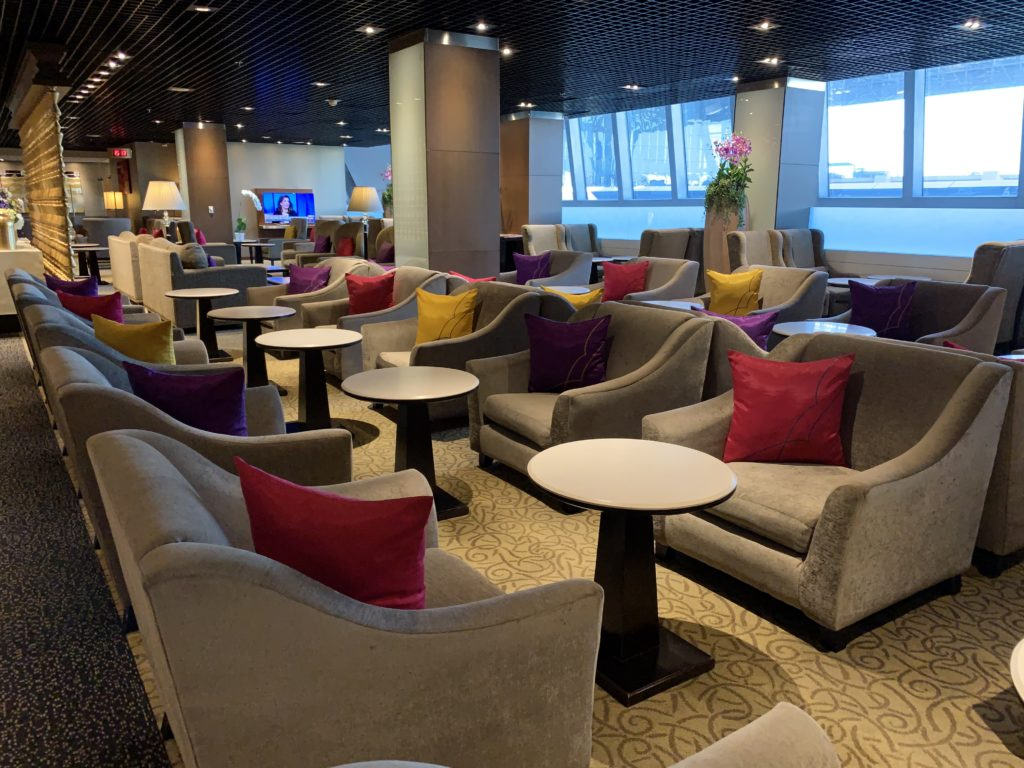 Rows of chairs and tables in the lounge. Different color pillows are seen on the chairs (yellow, purple, red)