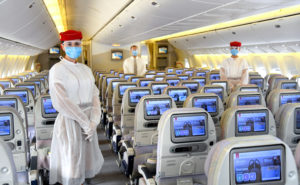 Emirates flight attendants in face masks, standing on board an Emirates aircraft
