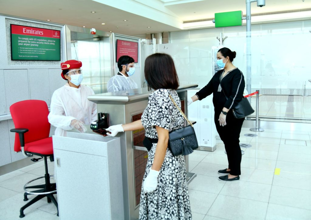 Emirates frontline employees, wearing face masks, check in passengers at the airport