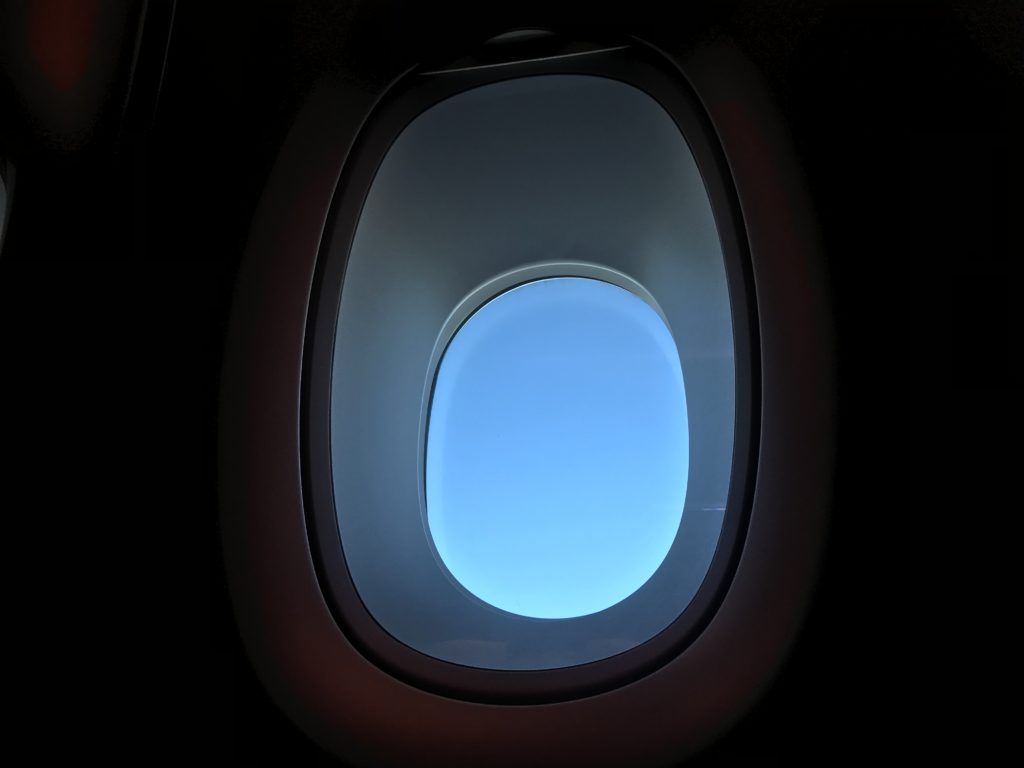 A serene scene of an aircraft window with a completely clear blue sky, taken from inside the aircraft cabin