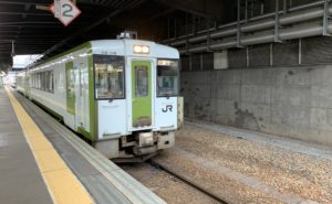 A third-sector train in white with a green door, coming through a tunnel