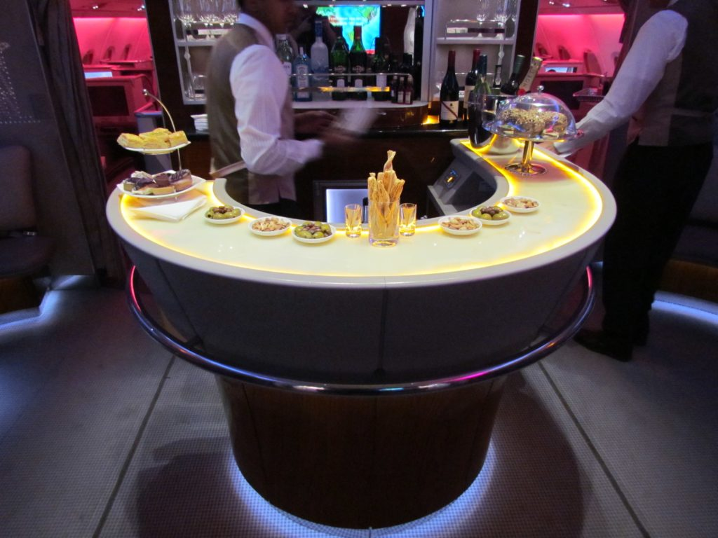 The spectacular Emirates rounded bar, with appetizers on offer, and a bartender behind, making drinks. There are bottles of different alcohol in the background. The bar is lit with a soft yellow.