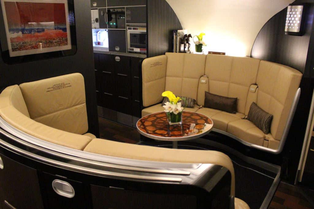 Two lounge sofas, in beige with brown pillows, are placed alongside Etihad's bar. A small circular coffee table is seen between the two sofas, with flowers in a jar on top