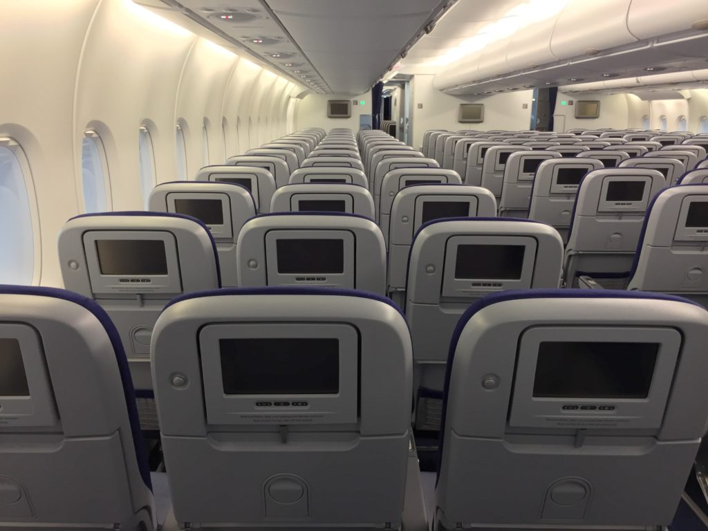 Rows of economy class seats, with seatback screens, aboard the A380