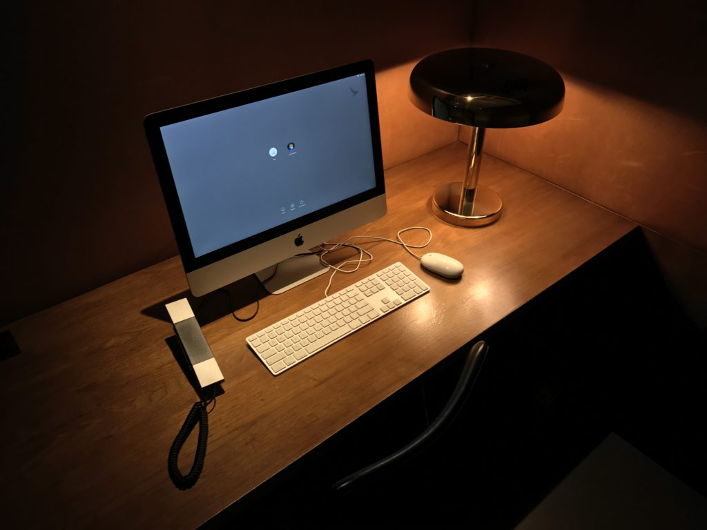 A computer, telephone and lamp on a desk, with low lighting