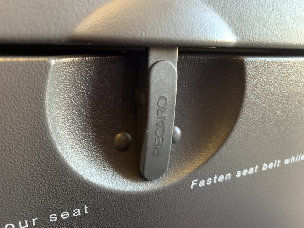 "The latch of an aircraft seat tray table, with the word ""Recaro"" on the latch"