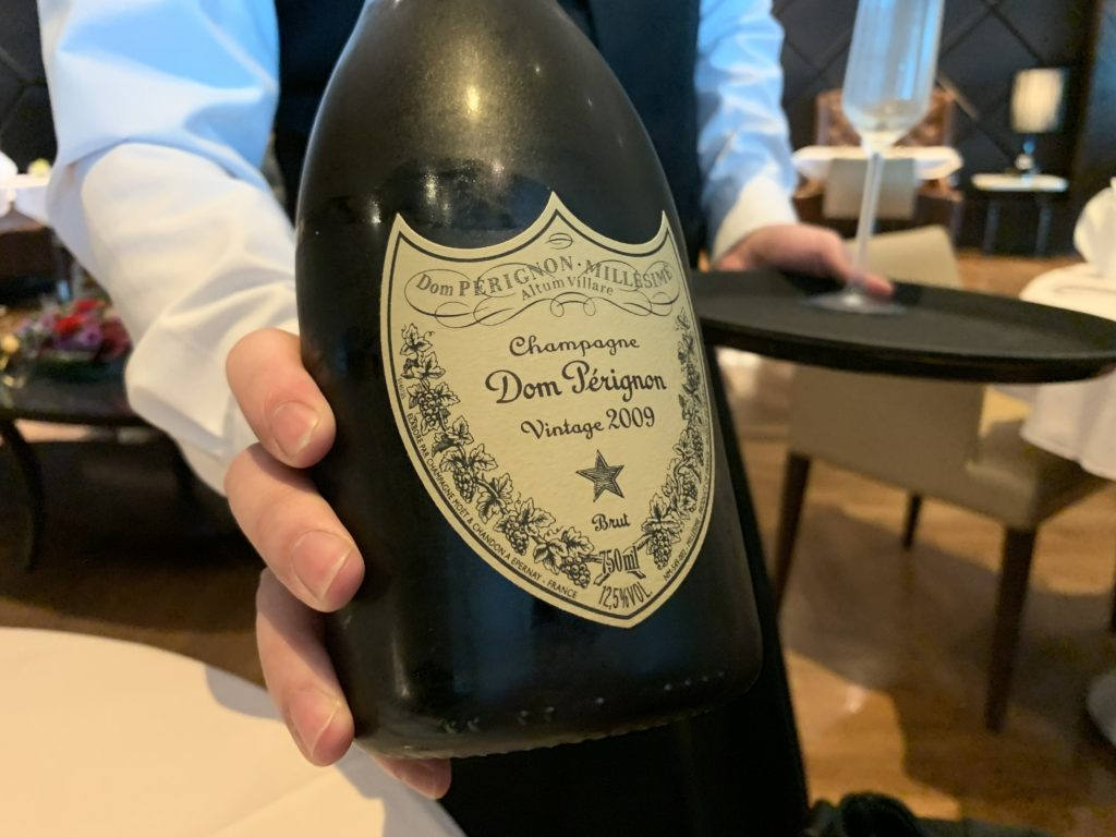 A lounge staffer showcases a bottle of Dom to the author, before pouring it into a stemmed glass