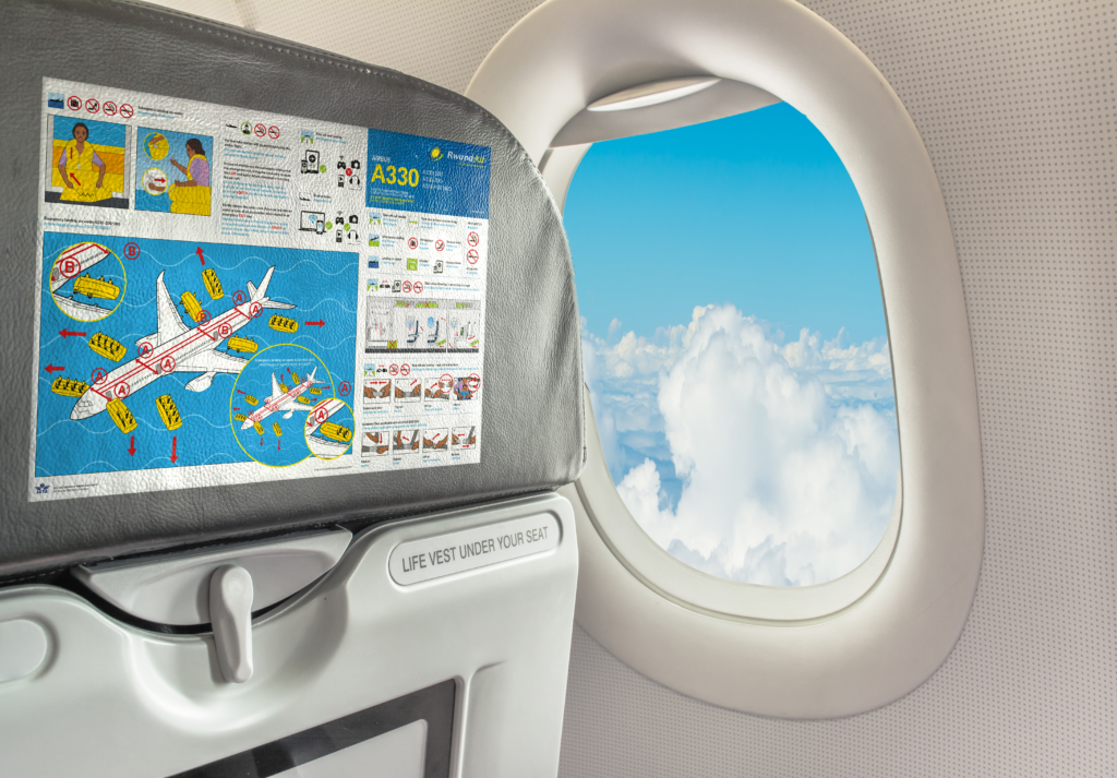 An embedded safety card is shown on the back of an aircraft seat. A blue sky and clouds are seen through the window.