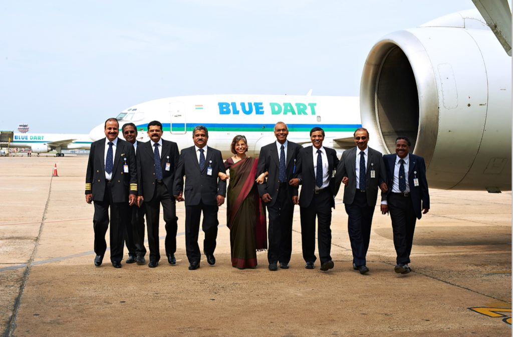 Blue Dart's managing director stands in front of a Blue Dart twinjet, arm-in-arm with the Blue Dart board of directors.