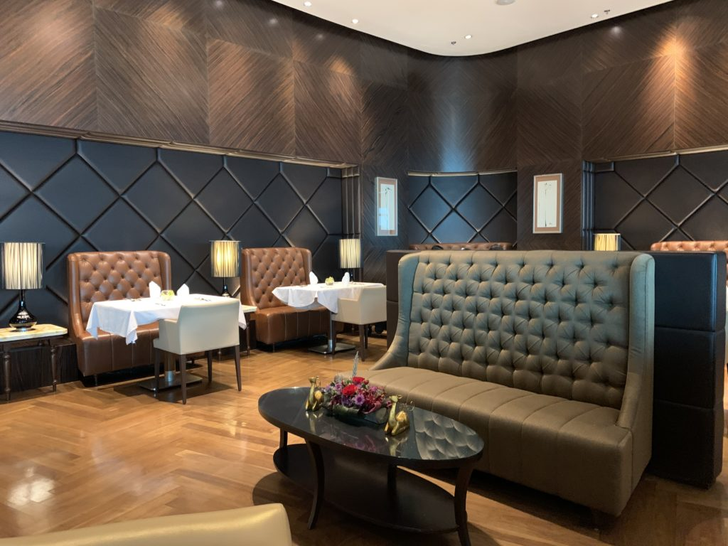 A tastefully decorated dining room with small tables, white table cloths and plush seating. The walls are decorated in a square design in deep brown