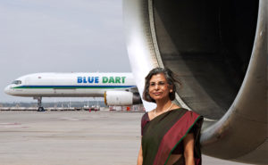 The managing director of Blue Dart, wearing a sari with a red sash, stands in front of a large jet engine. In the background is a Blue Dart 757.