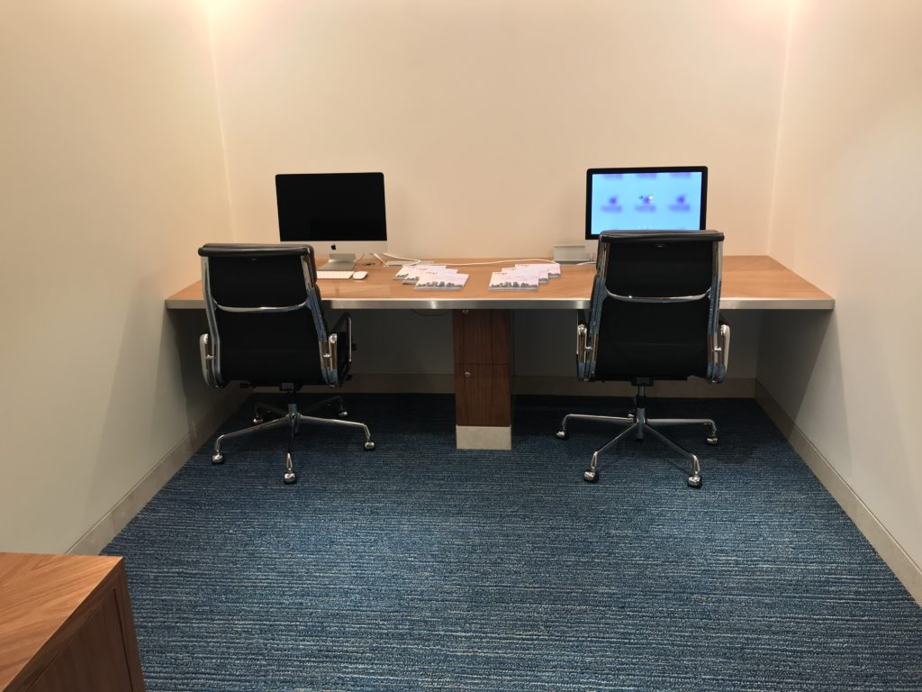 A bland room with no wall coverings, with a desk at the far end and two chairs and two computers