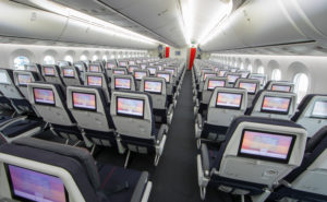 Rows of aircraft seats on board with seatback IFE screens