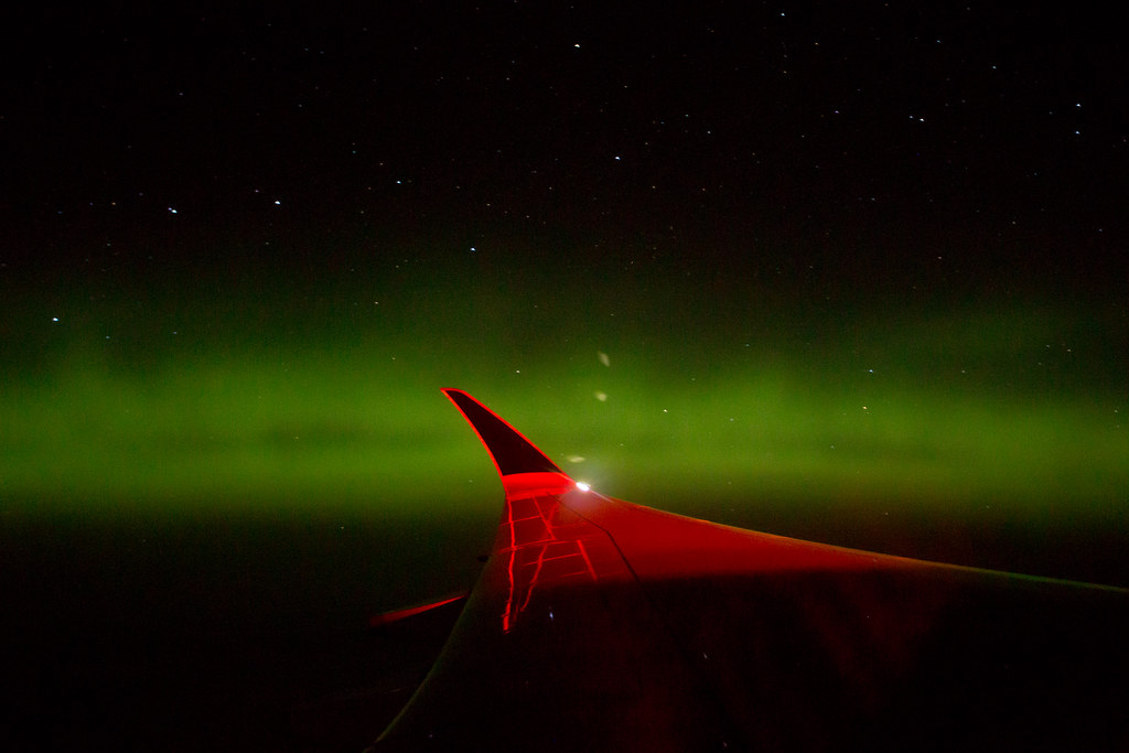 The wingtip of the A350ULR, lit in red, with a dark sky and a green light amid the darkness