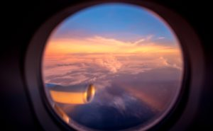 Sunset out the window of a Singapore Airlines A350, flying the world's longest route. Clouds and a beautiful pale yellow/pink light is seen in the sky